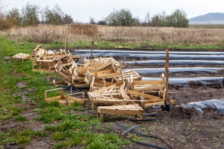Pile of wooden boxes stacked haotically at the side of agriculture field
