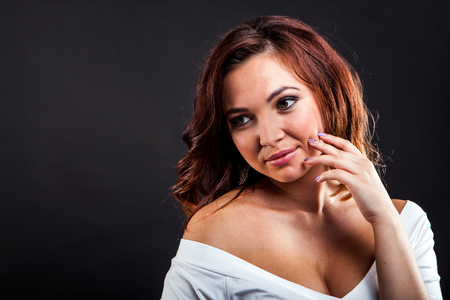 Portrait of attractive young woman on black background in studio