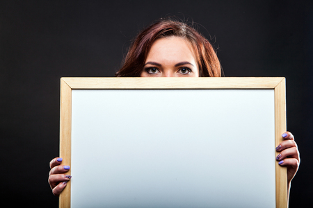 Portrait of attractive young woman holding office whiteboard on black background in studio