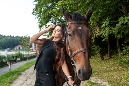 Pretty young woman and a brown horse outdoor