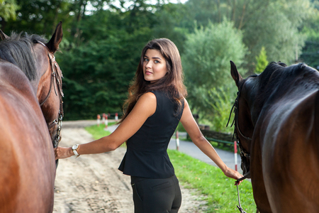 Pretty young woman walking two horses outdoor