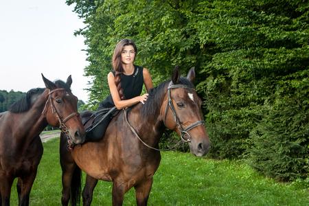 Hübsche junge Frau , die ein braunes Pferd im Freien reitet Standard-Bild - 98645271