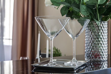 empty martini glasses and flower vase on kitchen counter Standard-Bild