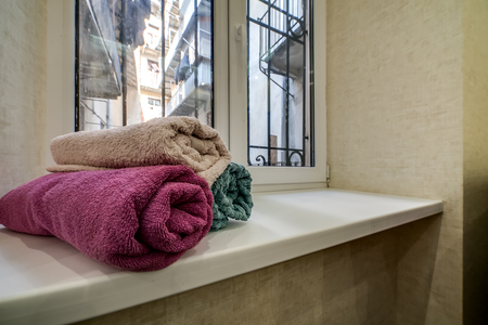 Stack of clean fresh towels on window sill