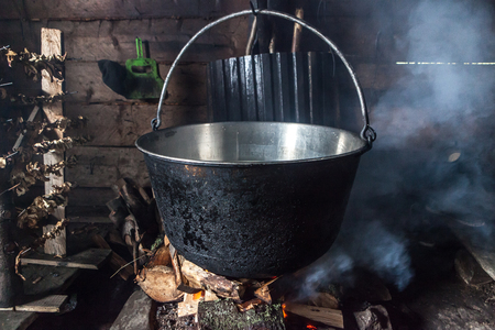 Steaming pot with soup over indoor fire in mountain hut Standard-Bild