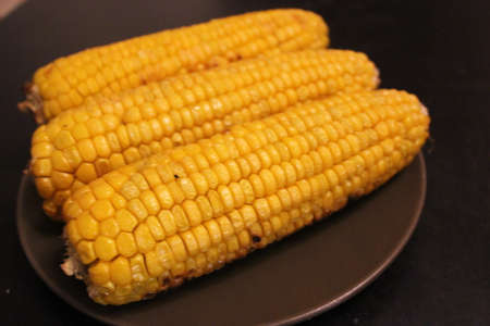 Three large boiled yellow corn lies on a plate on a dark background