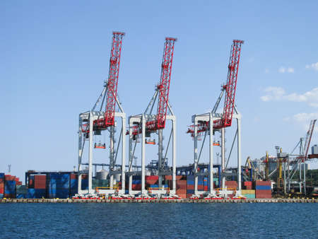 Portal container handlers at the berth edge are ready to work with a container ship