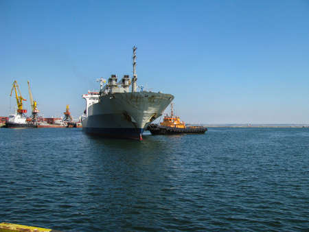 Port tug leads a dry cargo ship to the pier. The deck crew prepared for the mooring, according to the staffing table