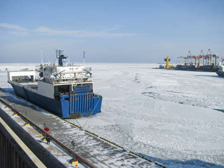 The Black Sea and the port water area are chained with ice. Dry cargo ship moored at berth Stock Photo