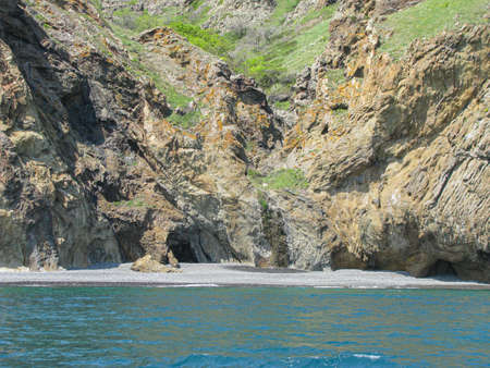 View of the steep Crimean coast from the sea, caves and ancient frozen lava flows