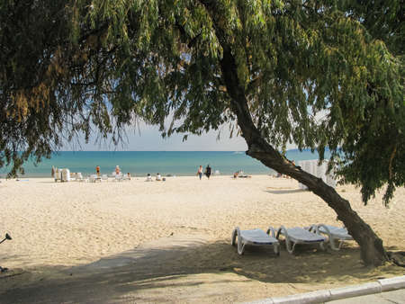 Odessa beach Luzanovka, an interesting view through an arch of trees. Sea, sand, vacationers 免版税图像