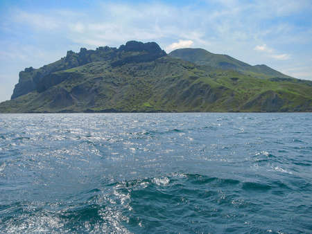 Crimea. View From The Sea To The Tele-Oba Ridge And Mount Lysuy, Kara-Dag Massif, Shrouded In A Light Haze, Near The City Of Feodossia