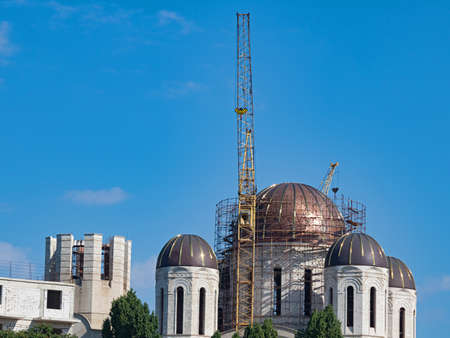 The Building of the Orthodox Church Under Construction, Surrounded by Scaffolding, Walkways and Cranes. The Dome of the Church Shines in The Sun