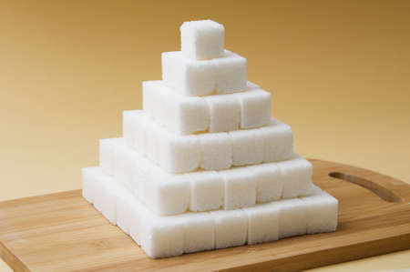 Sugar cubes pyramid on a yellow basckground photo