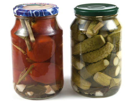 preserving: Preserved tomatoes and cucumbers in jars on a light background