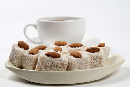 Turkish delight with almond nuts on a dish and tea photo