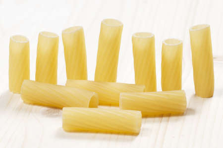 Penne pasta on a wooden table, close-up