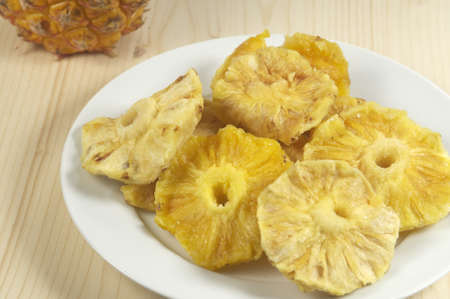 sundried: Sun-dried pineapple slices in a dish on a wooden table Stock Photo
