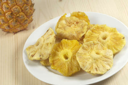 Sun-dried pineapple slices in a dish on a wooden table Stock Photo