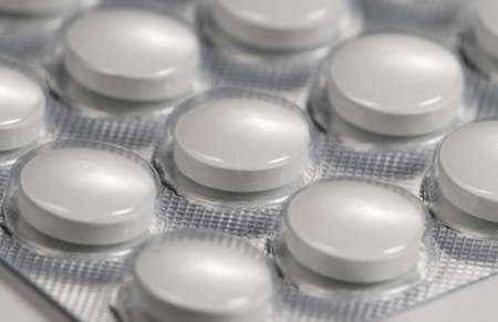 Tablets in blister over light background, macro shot