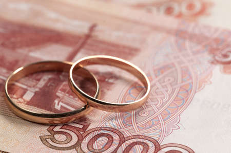 Wedding rings on money - marriage of convenience concept