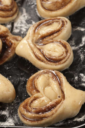 cookie sheet: Cinnamon buns ready for baking on a cookie sheet
