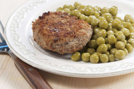 Cutlet with green peas, macro shot, local focus