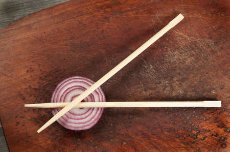 Still life with chopsticks and onion on a wooden board