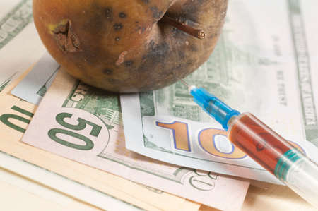 narcotic: Dead apple with syringe on dollars - concept Narcotic drugs kill