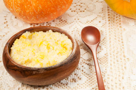 kasha: Rice kasha with pumpkin in a timber bowl Stock Photo