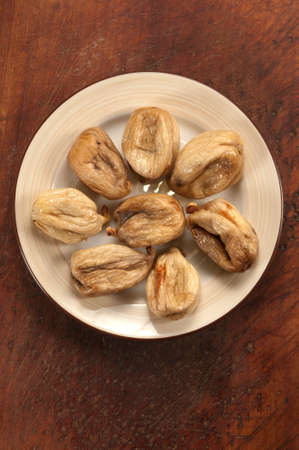 sun dried: Sun dried figs on a plate on timber board