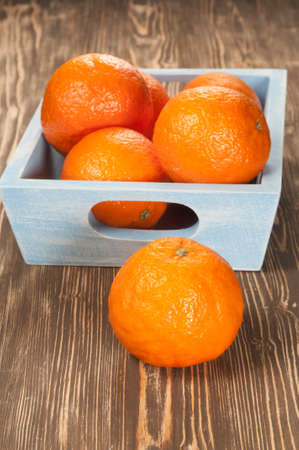 lifestile: Tangerine fruits in a timber box on a wooden table