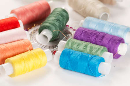 needlecraft product: Sewing strings and needles on a light background