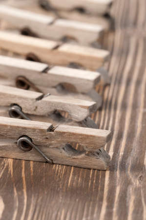 clothespeg: Old wooden clothes pins  on a timber board, close-up