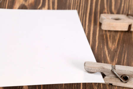 clothespeg: Old wooden clothes pins and blank paper on a timber board, close-up
