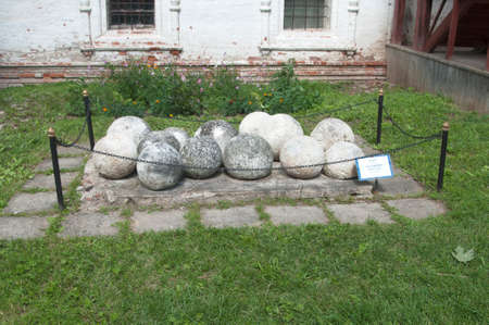 siege: PERESLAVL-ZALESSKY, RUSSIA, JULY 25, 2015 The former Goritsky Monastery of Dormition, (now Historical and Architectural Museum-Reservation). Stony cannon balls from the ancient siege guns (15 - 16 centuries) Stock Photo