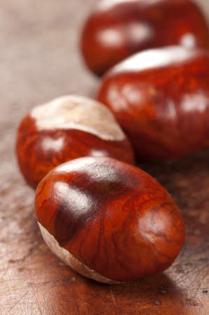 horse chestnuts: Horse chestnuts on a timber board, closeup shot Stock Photo