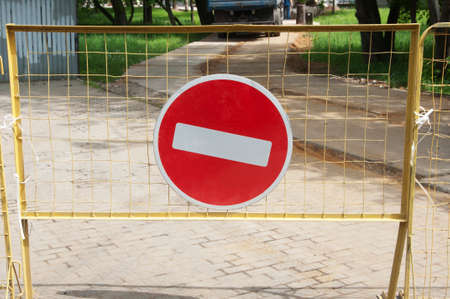 indicate: No ehtry road sign on a yellow metal fence Stock Photo