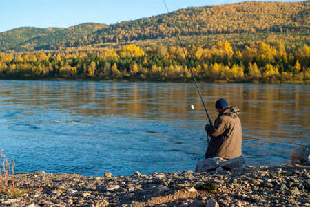 A fisherman with a fishing rod catches fish from a rocky shore on a sunny autumn day. Closeup of a river and mountains covered by forest in the background