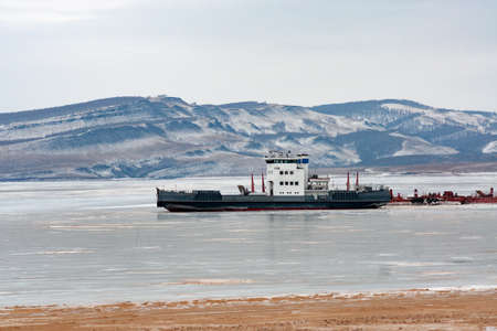 A large cargo ferry frozen into the ice near the pier on the Siberian river. Selective focus