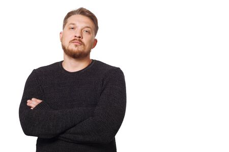 Man in a black sweater on a white background looks directly at the camera. Stock Photo