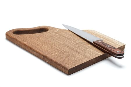 A large stainless steel cook knife with a wooden handle lies on a handmade cutting board made of solid oak Stock Photo