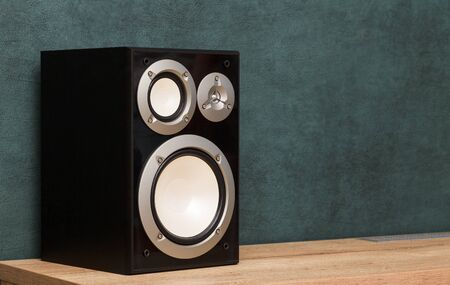 One modern black audio speaker system in interior on wooden desk near the dark green wall