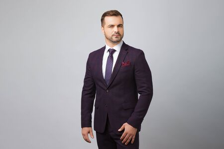 Successful man wear blue suit in gray background. Stock Photo