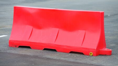 Red barriers made of plastic blocking the road. Do not cross.