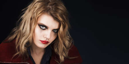 Halloween. Young girl in halloween stylized makeup on a dark background. Standard-Bild