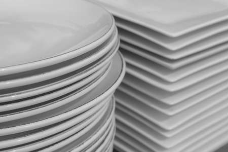 Stack of white porcelain crockery. Ceramic dishware pile.