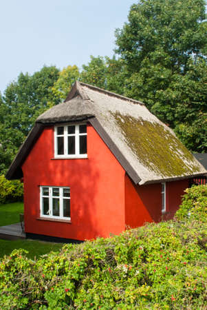 red cottage with thatched roof