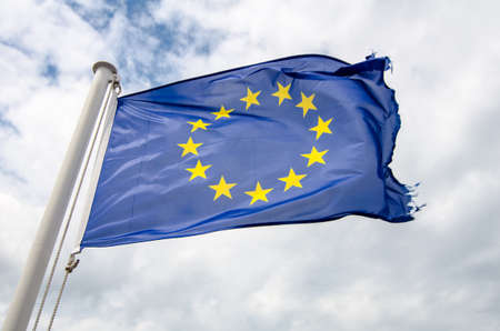 frayed european flag in the wind