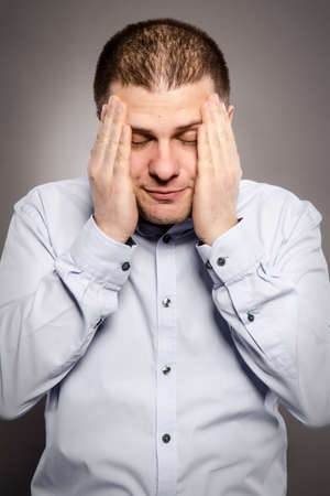 sobbing: a man is suffering from very strong headaches